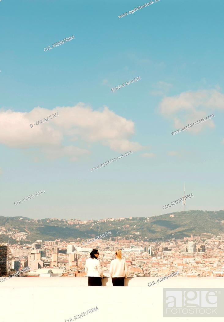 Stock Photo: Rear view of female tourists looking out over cityscape, Barcelona, Spain.