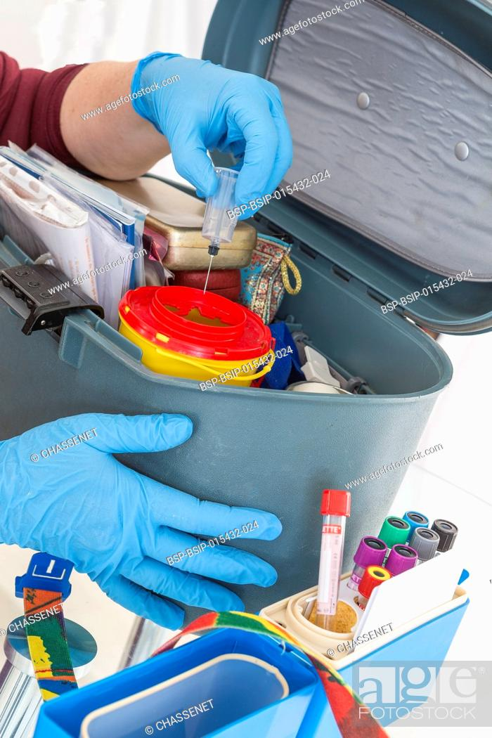 Stock Photo: Nurse organising her First aid briefcase medical tools . Assistance equipment on white.
