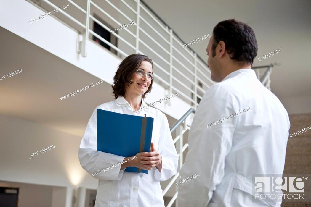Stock Photo: Two doctors talking on a staircase.