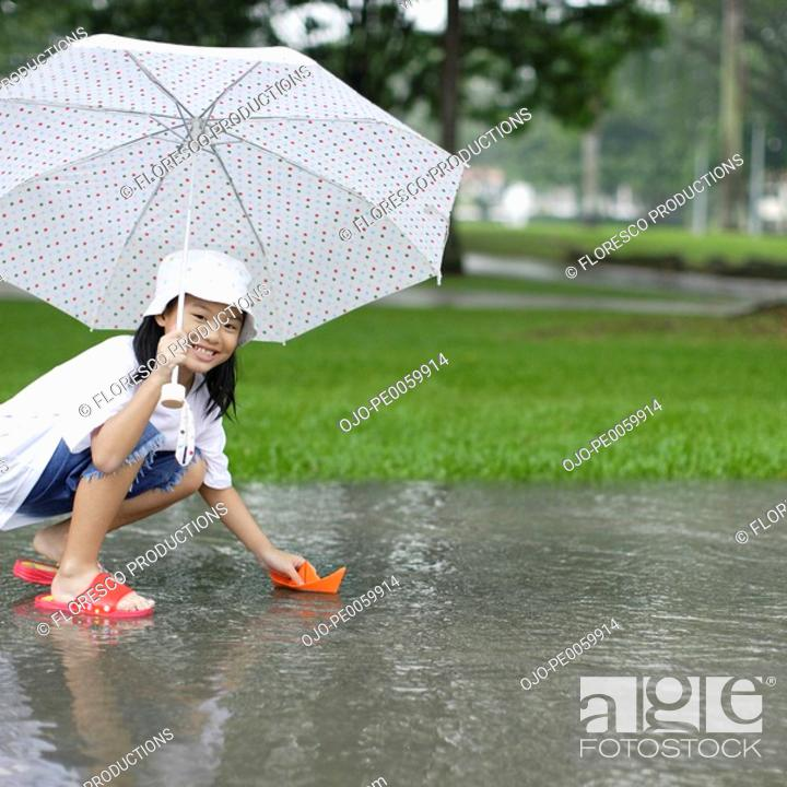 Stock Photo: Young girl outdoors in rain playing with paper boat.