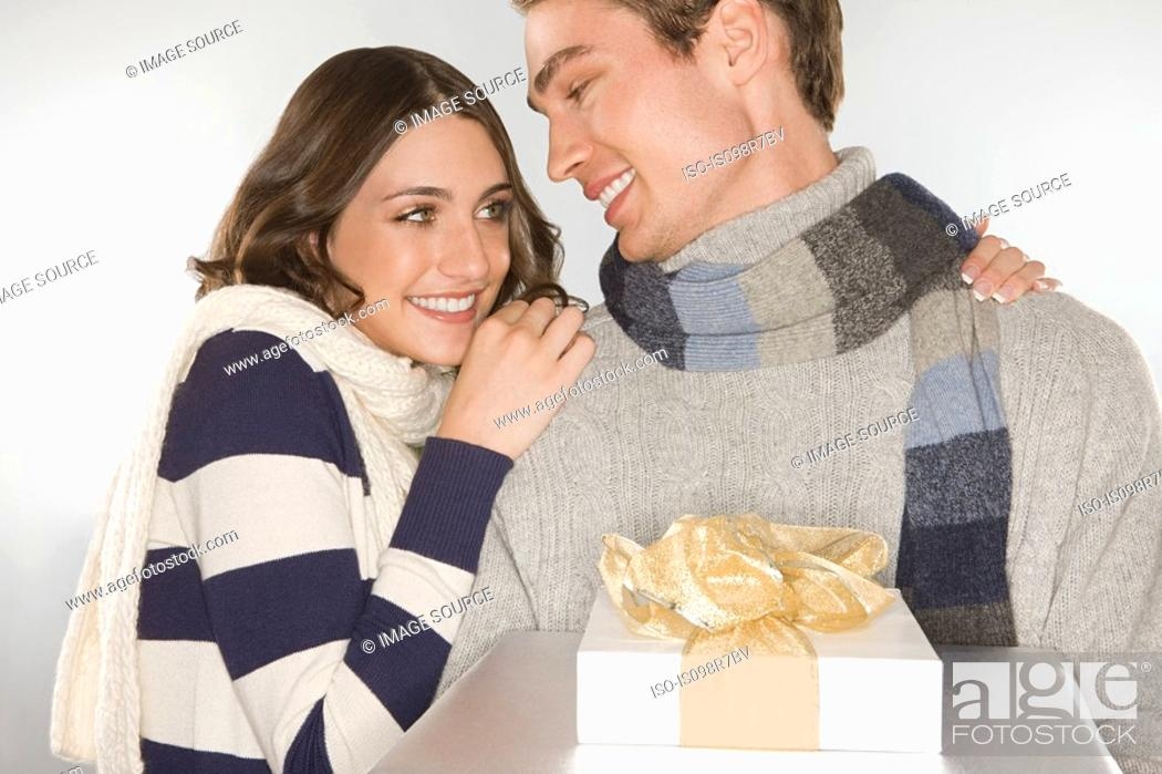 Stock Photo: Happy young couple holding a gift.