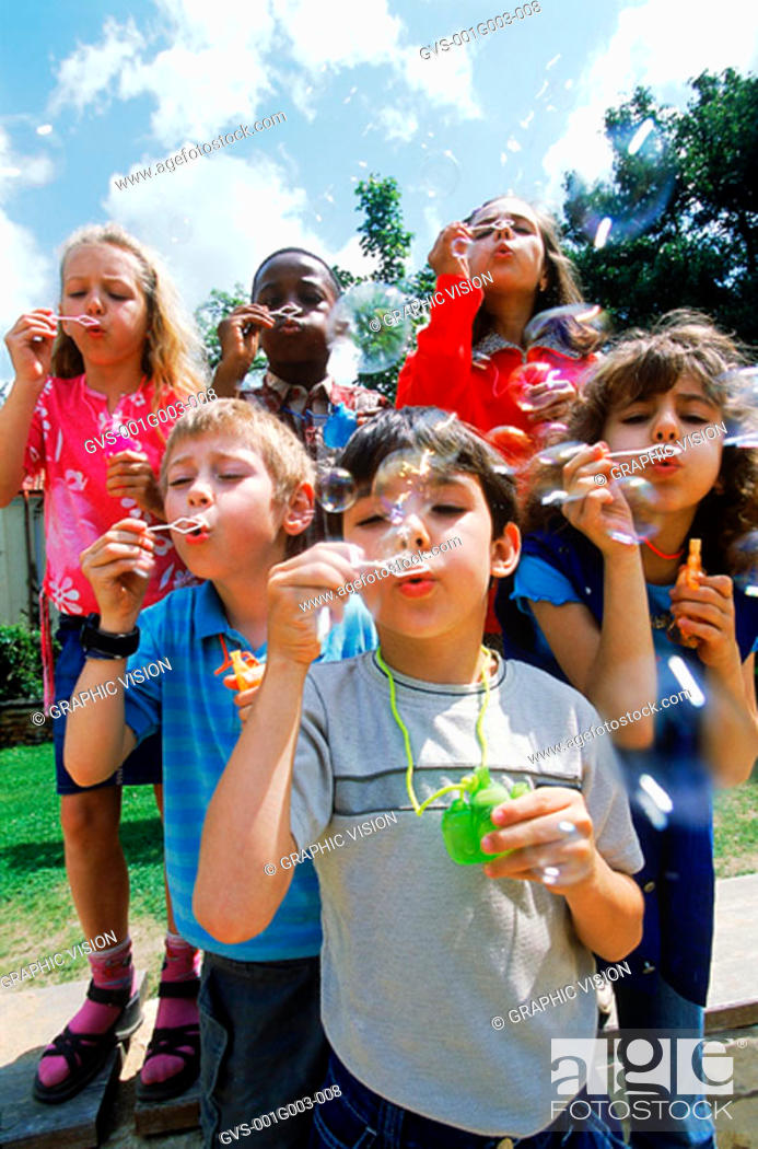 Stock Photo: Young children blowing soap bubbles.