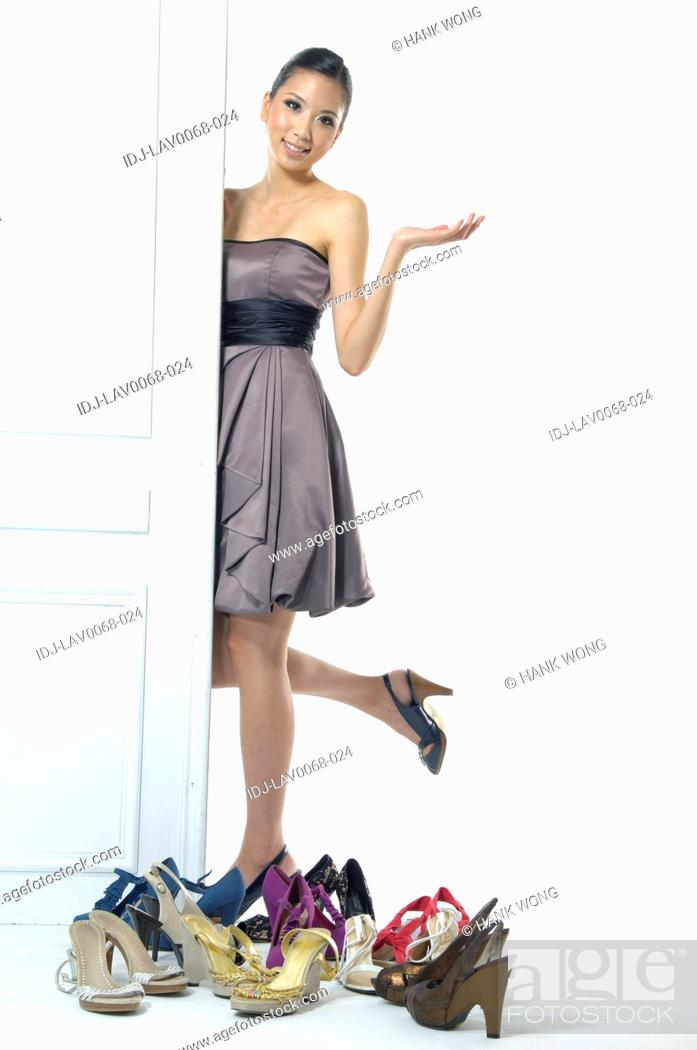 Stock Photo: Woman standing beside a door near a collection of footwear.