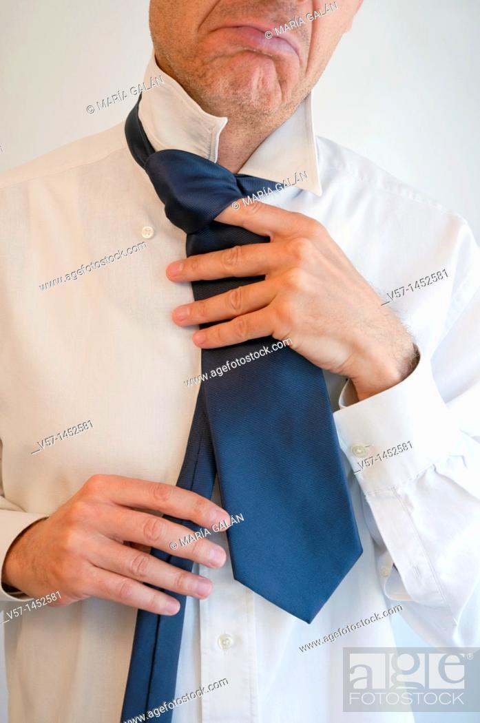 Stock Photo: Man tying his necktie badly. Close view.