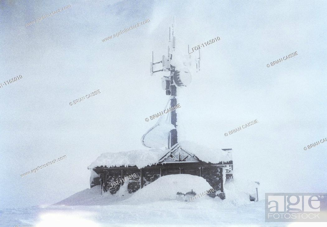 Stock Photo: A building with a large antenna covered in snow.
