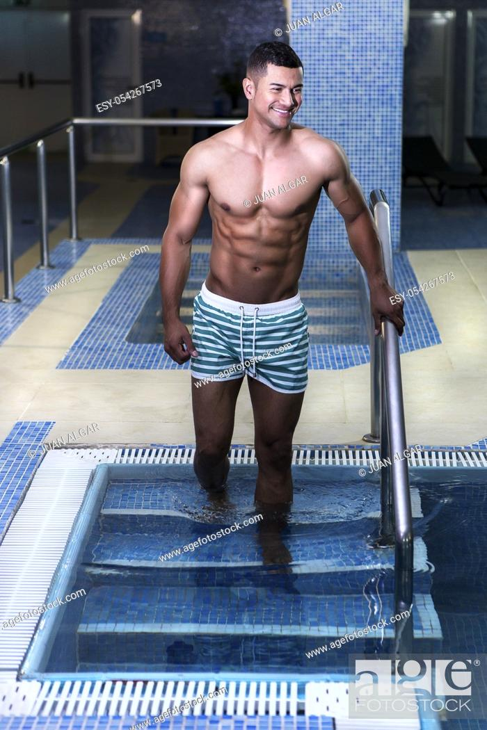 Stock Photo: Handsome muscular man walking into pool and smiling. Vertical indoors shot.
