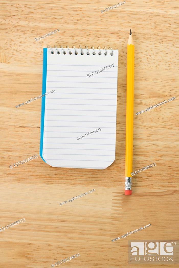 Stock Photo: Pencil beside open spiral bound notepad.