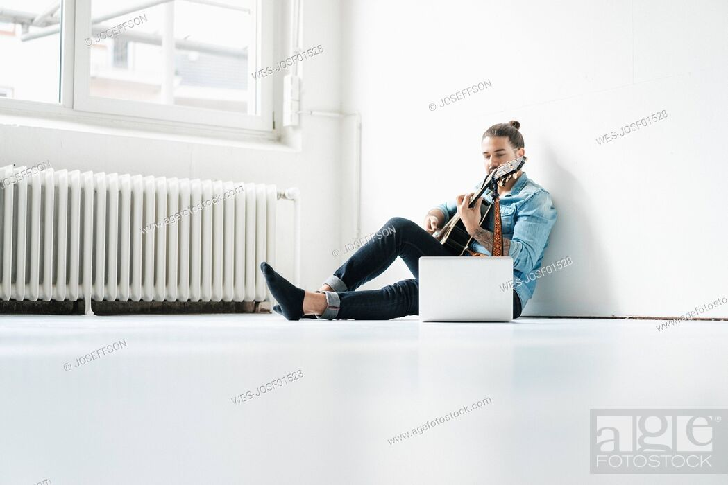 Stock Photo: Man sitting with laptop on floor playing guitar.