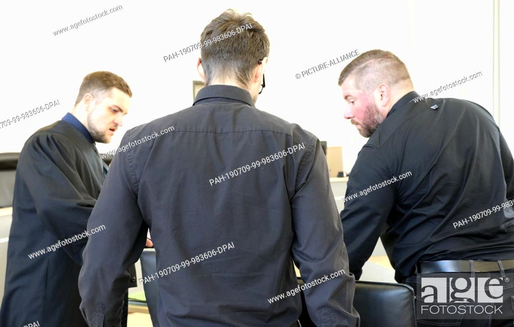 Stock Photo: 09 July 2019, Mecklenburg-Western Pomerania, Rostock: The 28-year-old defendant (M) in the trial for attempted double homicide is waiting with his defenders.
