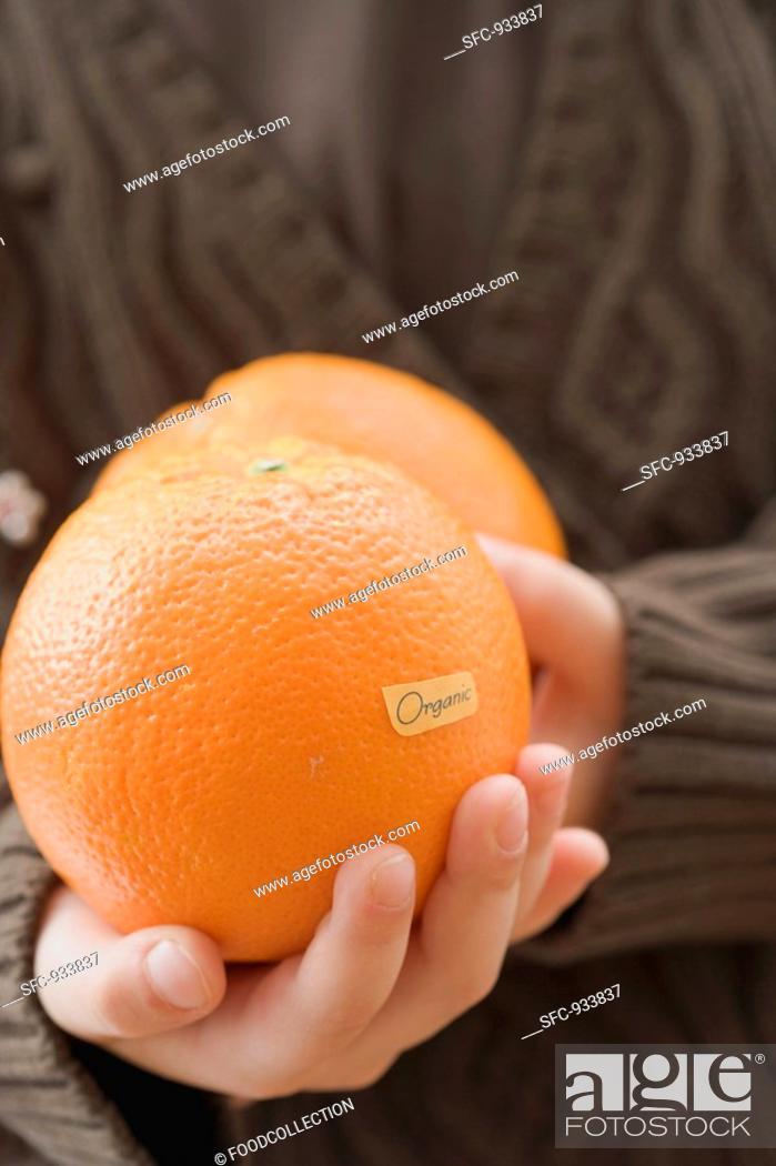 Stock Photo: Girl holding organic oranges.
