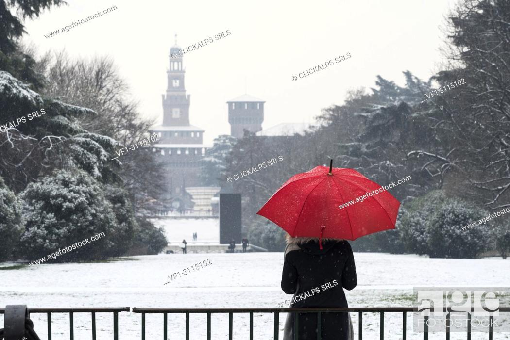 Stock Photo: A woman with red umbrella admires the view of Sempione park during a snowfall. Milan, Lombardy, Italy, Europe.
