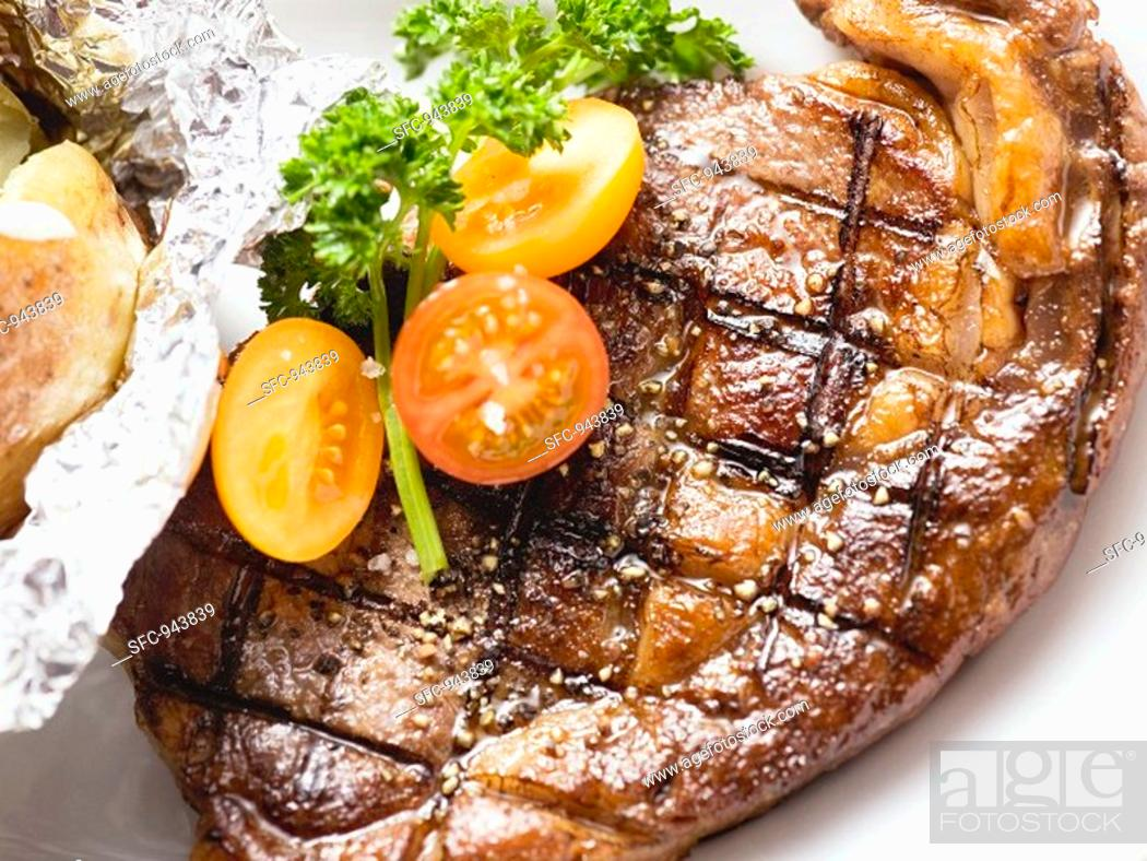 Stock Photo: Grilled rump steak with tomatoes and baked potato.