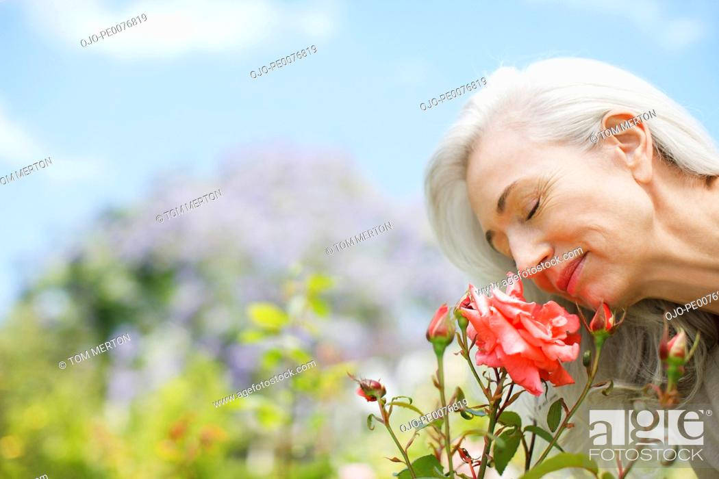 Stock Photo: Woman smelling rose.