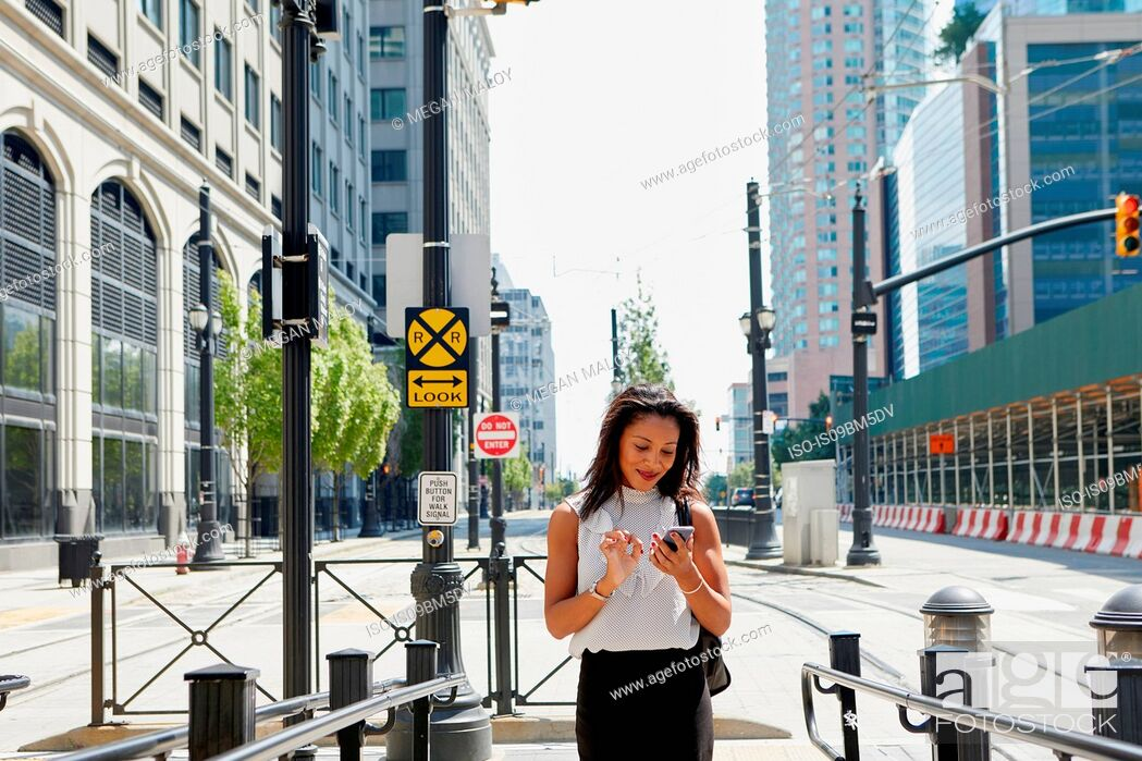 Stock Photo: Businesswoman using cellphone by barriers.