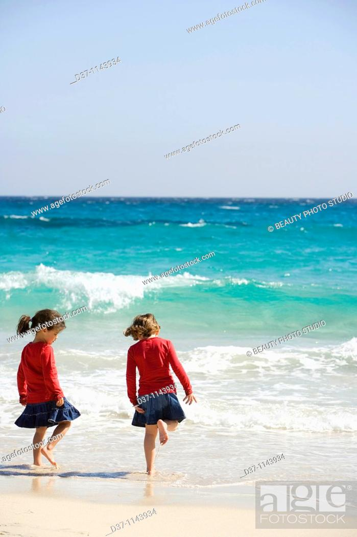 Stock Photo: Two caucasian girls by the sea playing.