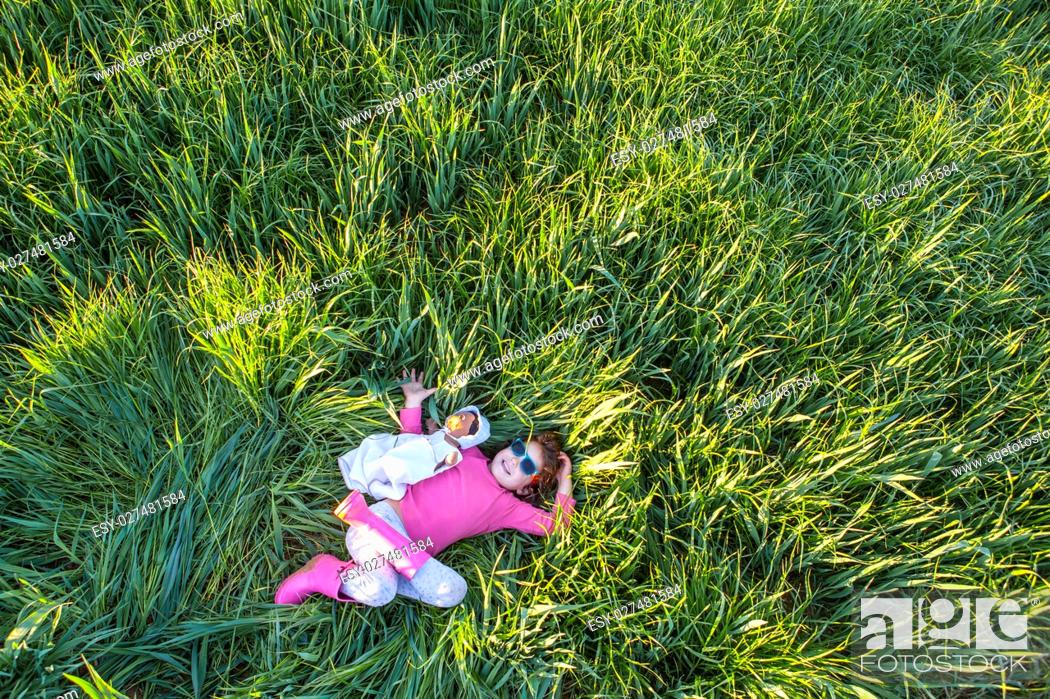 Stock Photo: Little girl and her doll lying on green cereal field at sunset, Spain.