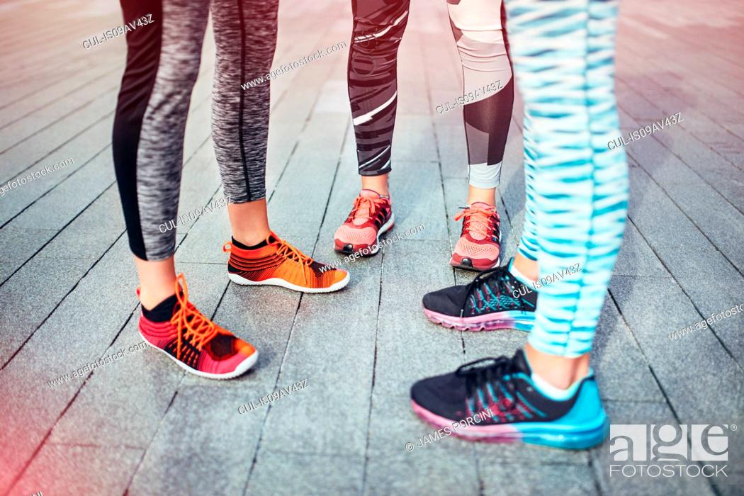 Stock Photo: Legs of three female runners standing on wooden pier.