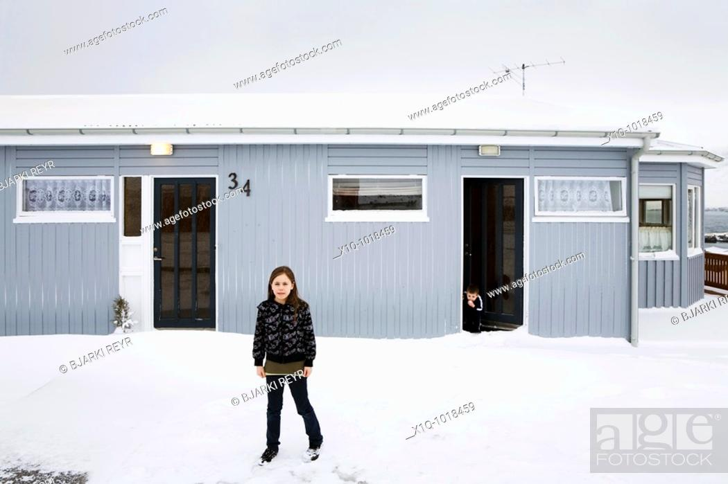 Stock Photo: Bryndis 9 standing outside her home, her brother Matthias 2 standing in the doorway  Vopnafjordur, East Iceland  Vopnafjordur hopes to service the oil industry.