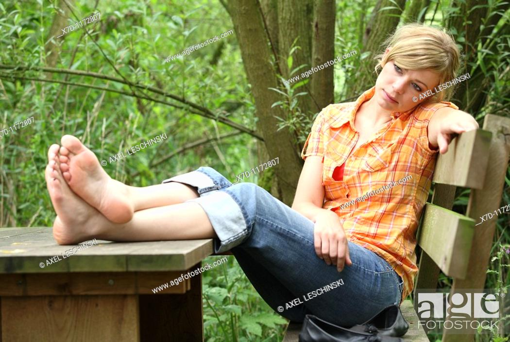 Stock Photo: blond woman sitting on bench resting with legs on table.