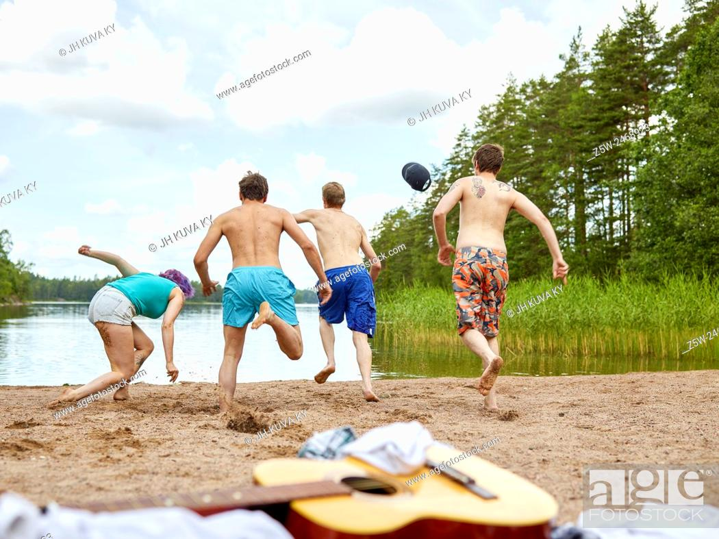 Stock Photo: The group of the people runs in the lake, summer day. Shot in southern Finland.