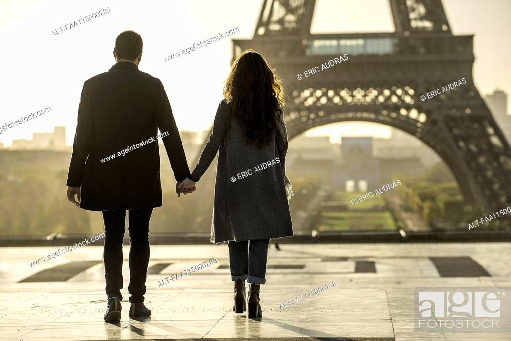 Stock Photo: Couple holding hands near Eiffel Tower.