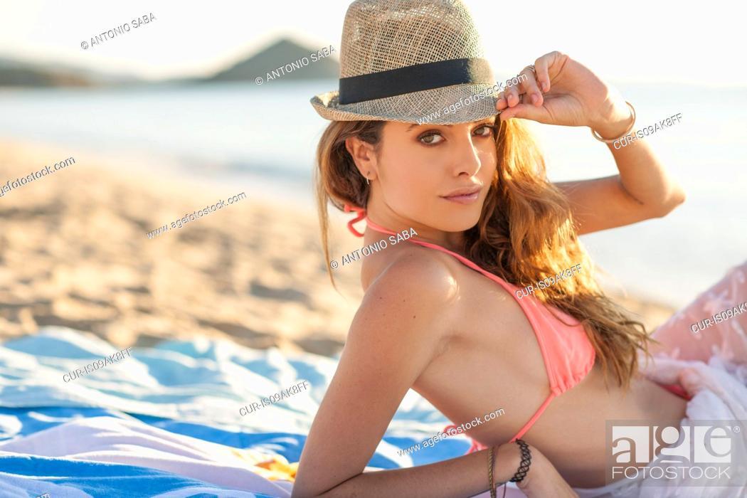 Stock Photo: Portrait of young woman sunbathing on beach, Castiadas, Sardinia, Italy.