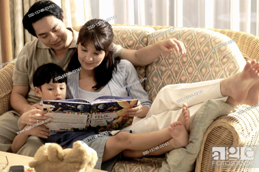 Stock Photo: Parents with their son reading a book.