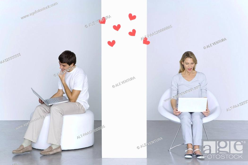 Stock Photo: Man and woman using laptop computers, hearts floating in the air between them.