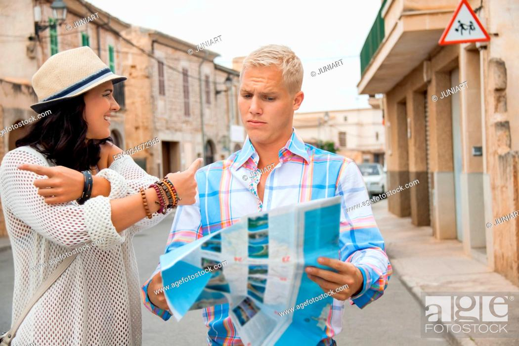 Stock Photo: Trendy attractive young couple of tourists consulting a map as they search for their destination while out sightseeing on their summer vacation.