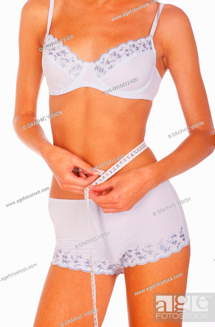 Stock Photo: Young woman standing in underwear measuring her waist.