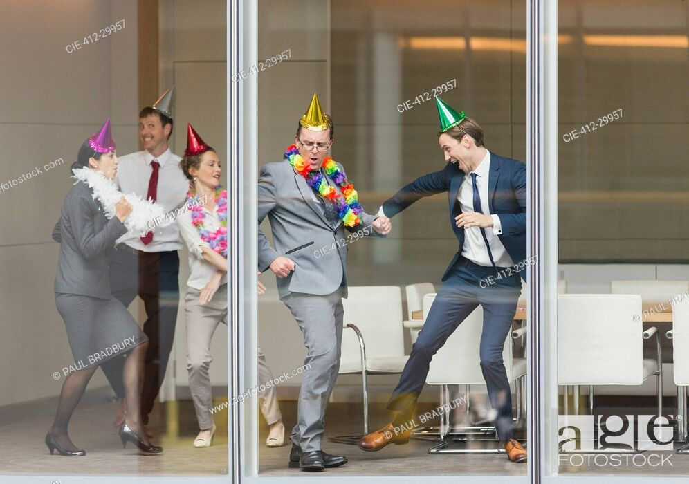 Imagen: Playful business people in party hats dancing at conference room window.