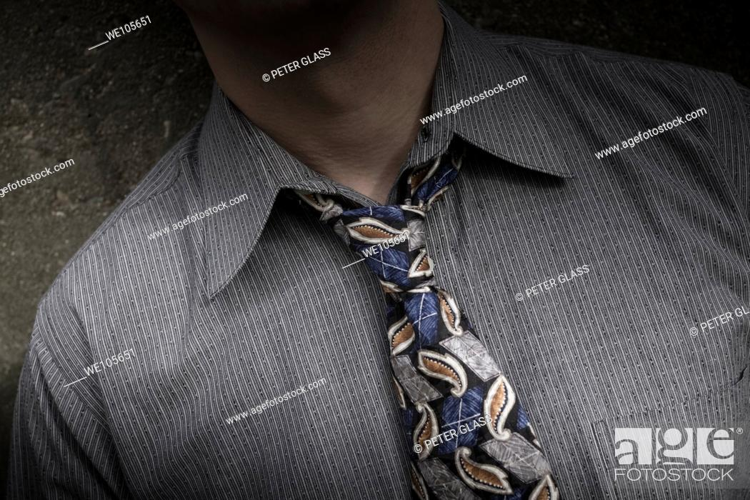 Stock Photo: Close-up of a young man with a loosened tie.