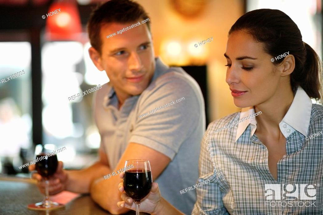 Stock Photo: Young couple drinking red wine in cafe, Paris, France.