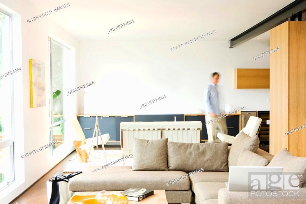 Stock Photo: Man walking through living room.
