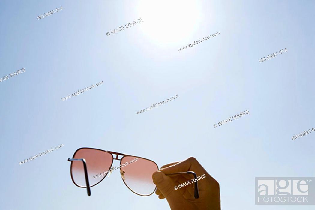 Stock Photo: Person holding sunglasses.
