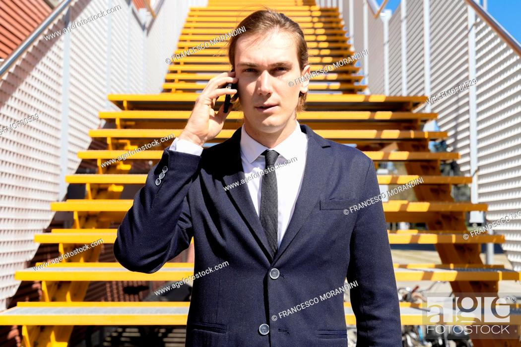 Stock Photo: Italy, Florence, young businessman on smartphone outdoor.