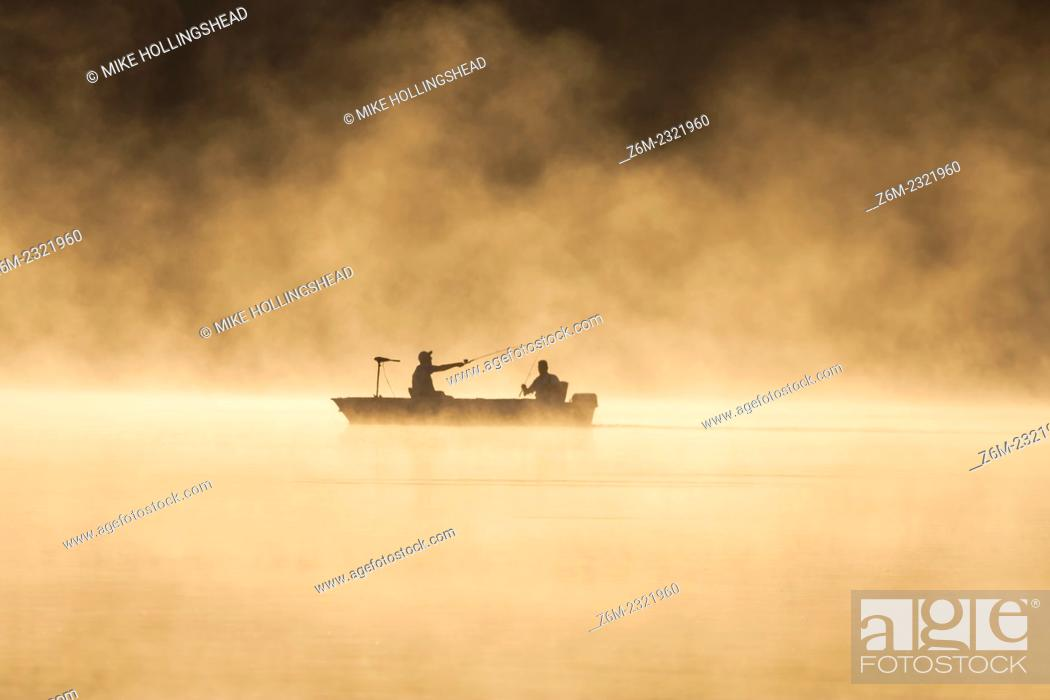 Stock Photo: Men fish on a steamy lake August 29, 2008 in western Iowa.