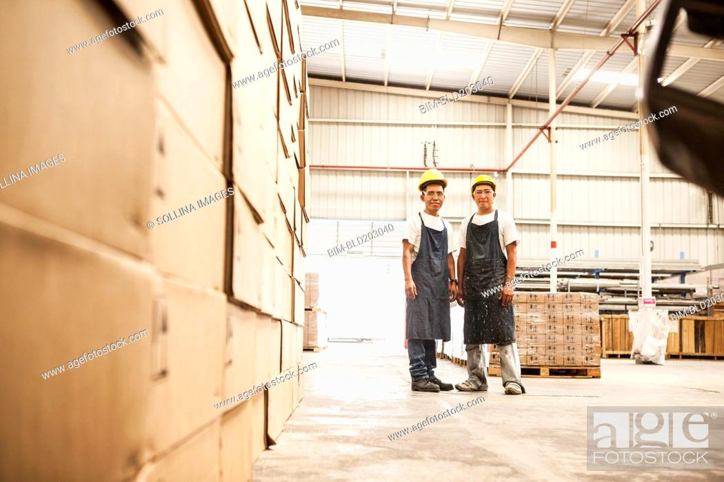 Stock Photo: Workers standing in manufacturing plant.