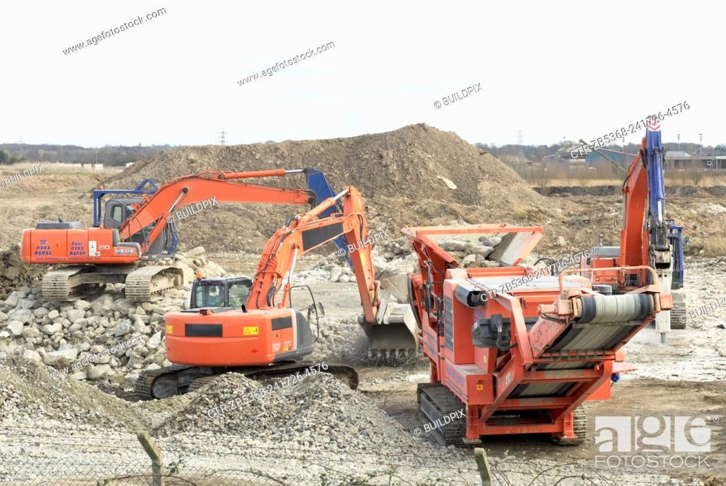 Stock Photo: Excavator clearing a demolished site with an aggregate Crusher, to make way for a paper recycling plant in Kings Lynn, Norfolk, UK.