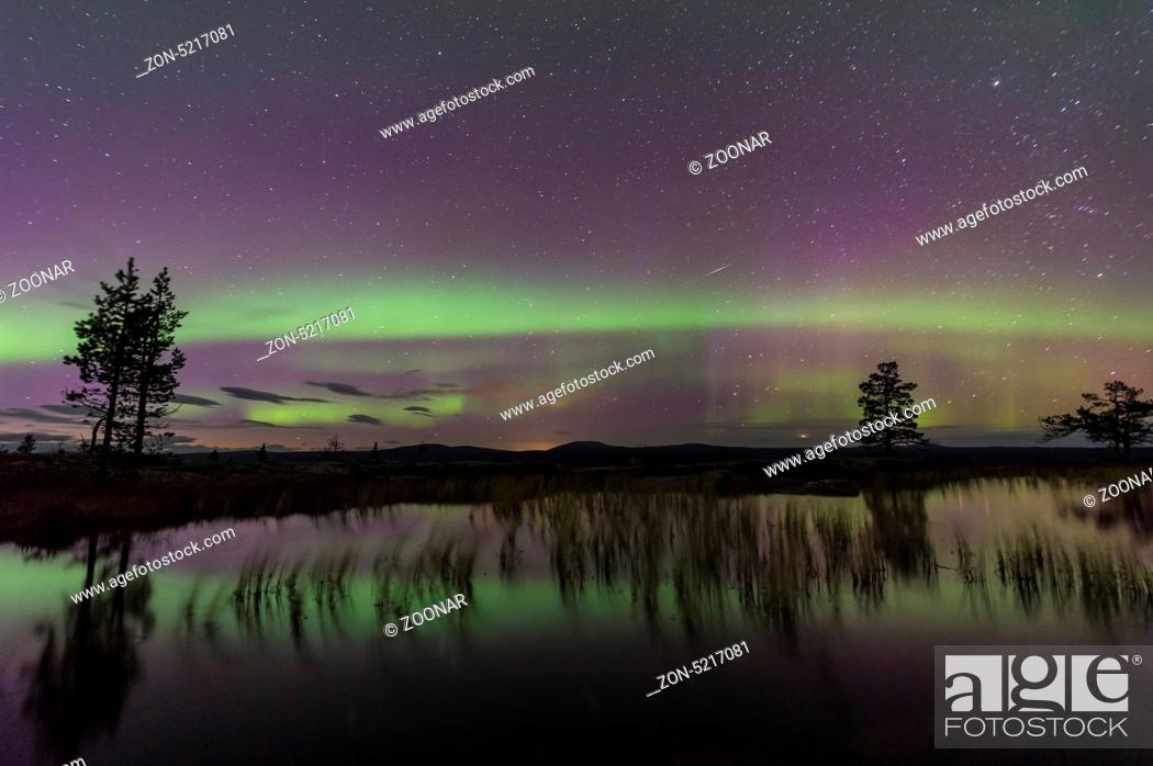 Stock Photo: Northern lights reflecting in a lake, Sweden.