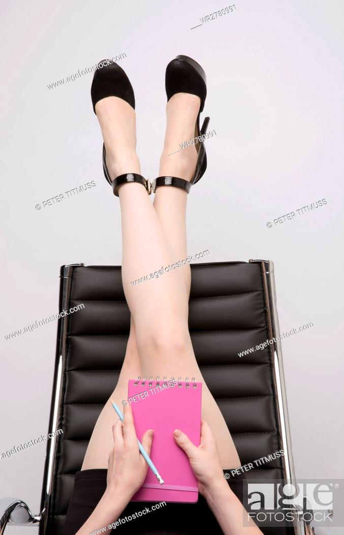 Stock Photo: Secretary taking time out with her legs stretching exercise on the back of an office chair.