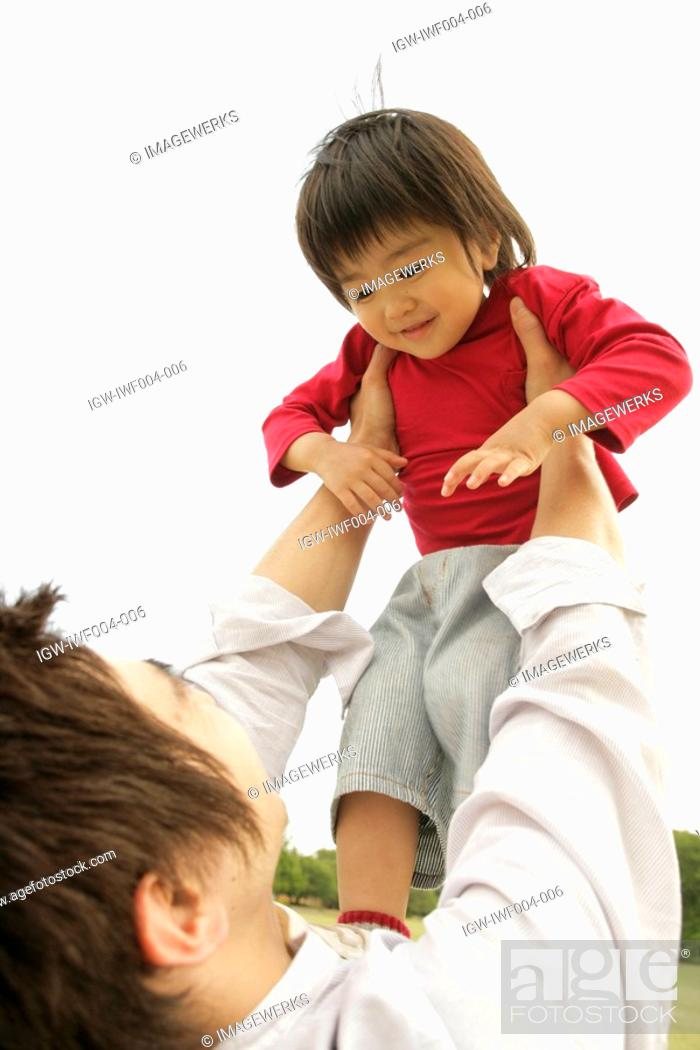 Stock Photo: A father lifting his son in air.