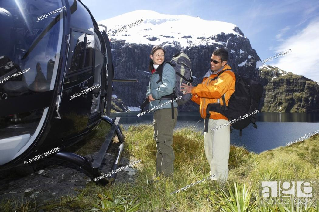 Stock Photo: Man adjusting woman's backpack next to helicopter on mountain peak.