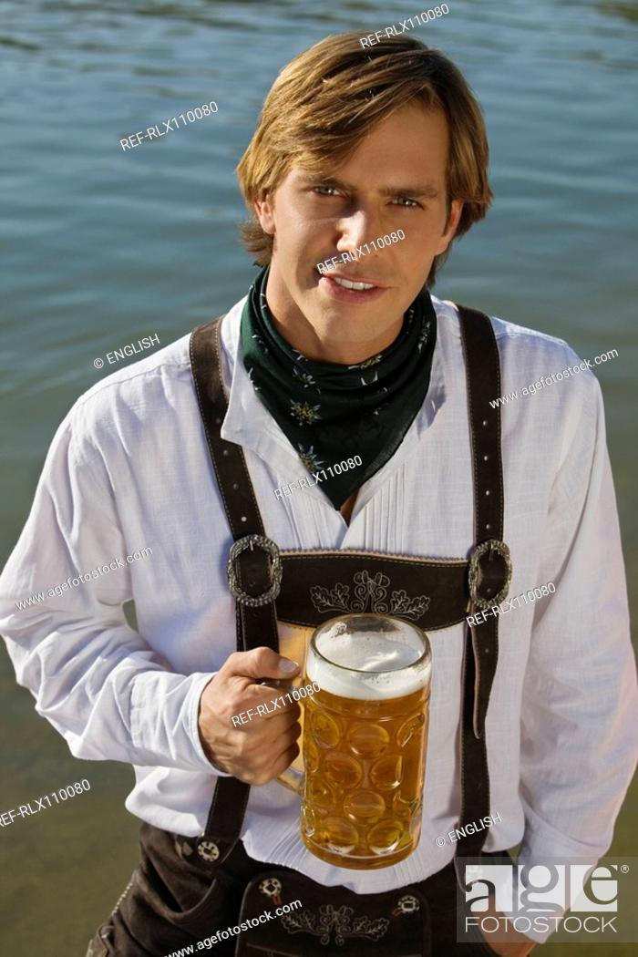Stock Photo: Young man in traditional Bavarian outfit, holding litre glass of beer, Munich.