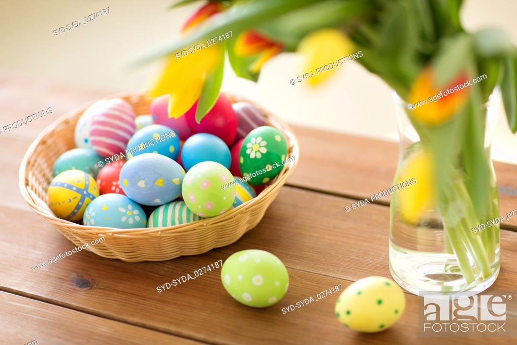 Stock Photo: colored easter eggs in basket and flowers at home.