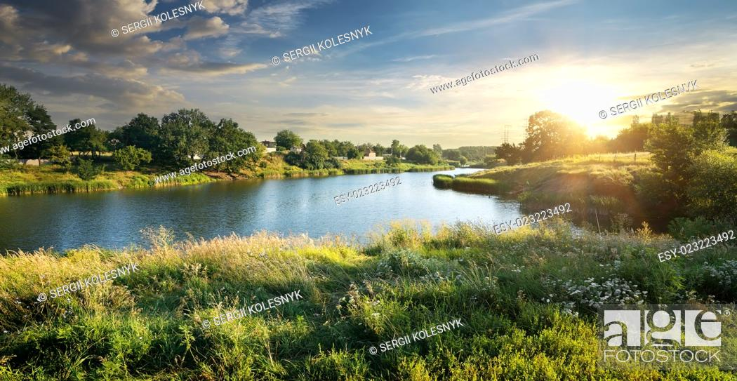 Stock Photo: Blue river under clouds at the sunset.