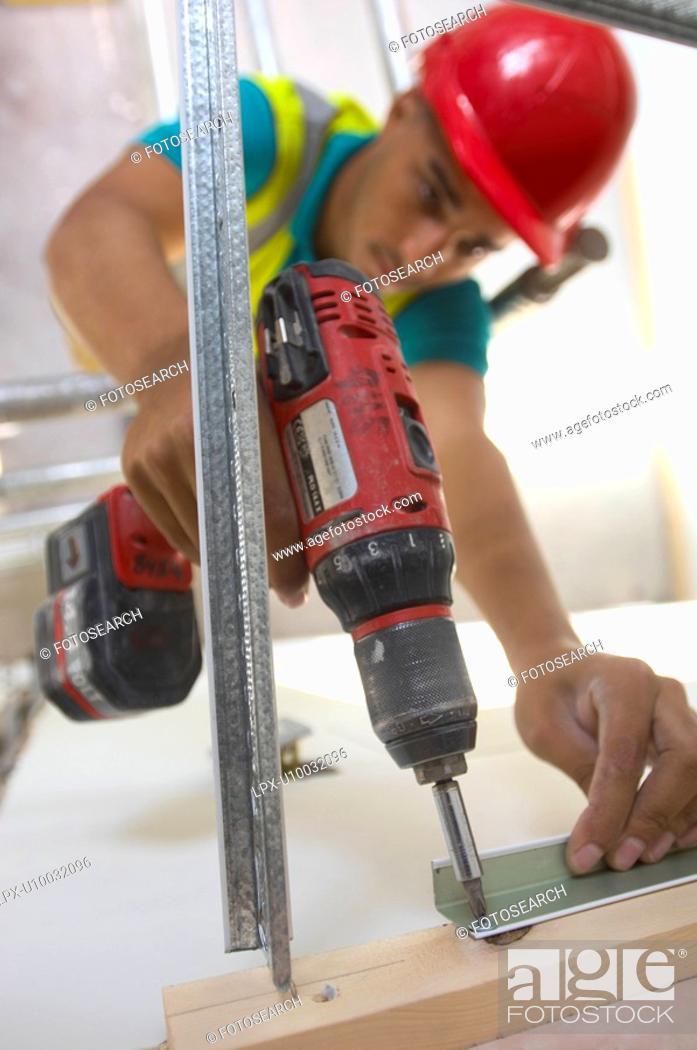 Stock Photo: Builder using power drill.
