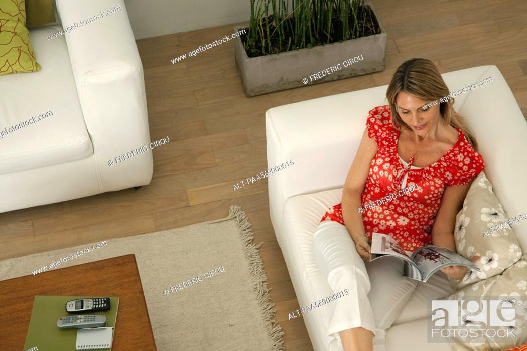 Stock Photo: Woman relaxing in living room reading magazine.