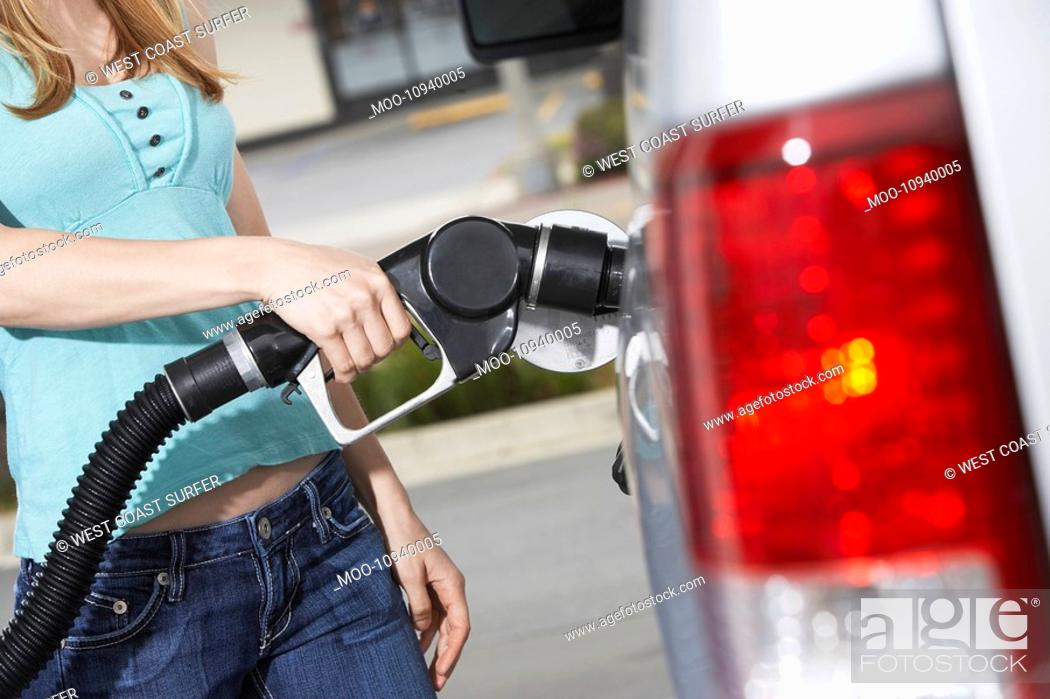 Stock Photo: Young woman filling car with gas at gas station mid section.