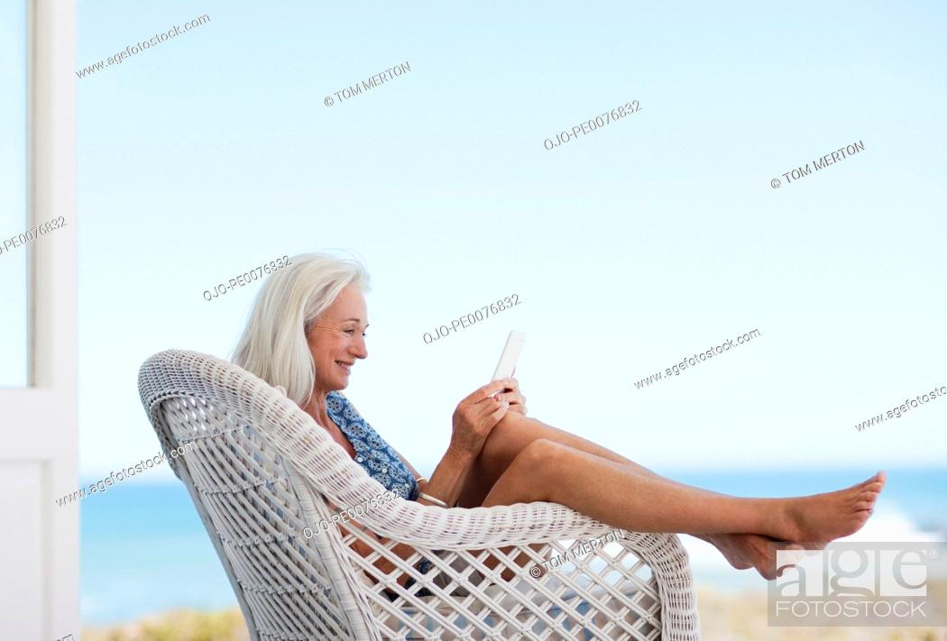 Stock Photo: Senior woman using digital tablet in chair.